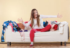 Woman sitting on sofa in messy room at home. Stock Photo