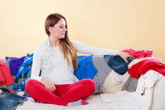Woman sitting on sofa in messy room at home. Royalty Free Stock Images