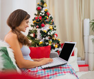 Woman sitting on sofa near Christmas tree Stock Photography