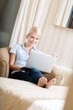 Woman sitting on the sofa with pc Stock Photography