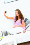 Woman sitting on sofa and photographing herself Royalty Free Stock Image