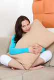 Woman sitting on a sofa with a pillow Stock Photos