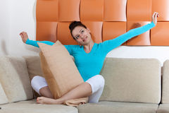 Woman sitting on a sofa with a pillow Royalty Free Stock Photography