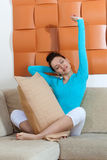 Woman sitting on a sofa with a pillow Stock Photo
