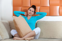 Woman sitting on a sofa with a pillow Stock Image