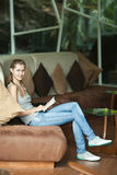 Woman sitting on sofa and reading book Royalty Free Stock Photography