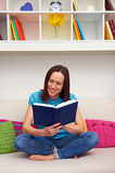 Woman sitting on sofa and reading the book Stock Photography