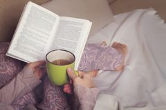 Woman sitting on sofa, reading book and drink Royalty Free Stock Images