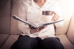 Woman is sitting on a sofa and reading a book while holding a co Stock Photos