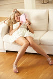 Woman Sitting On Sofa Reading Diary Royalty Free Stock Image