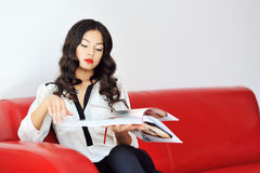 Woman sitting on a sofa and reading magazine Royalty Free Stock Image