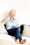 Woman sitting on the sofa reads a book Royalty Free Stock Images