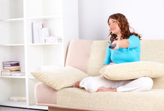 Woman sitting on sofa with remote controller Royalty Free Stock Photo