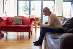 Woman Sitting On Sofa Sending Text Message On Phone Royalty Free Stock Images