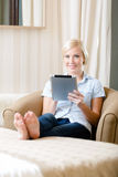 Woman sitting on the sofa with silver pad Stock Photos