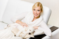 Woman sitting on the sofa with sleeping labrador puppy Royalty Free Stock Image