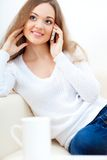 Woman sitting on sofa and talking by phone Stock Images