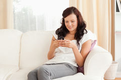 Woman sitting on a sofa while texting Stock Photos