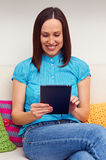 Woman sitting on sofa and using her touch pad Royalty Free Stock Photos