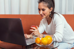 Woman sitting on the sofa using a laptop computer at home. Royalty Free Stock Images