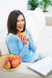 Woman sitting on sofa using laptop. Royalty Free Stock Photo