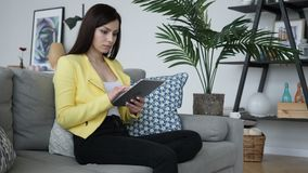 Woman sitting on sofa using tablet for internet browsing. 4k , high quality stock video
