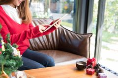 Woman sitting on sofa using tablet pc at home. girl texting mess Stock Image