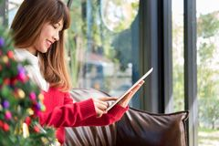 Woman sitting on sofa using tablet pc at home. girl texting mess Royalty Free Stock Image