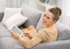 Woman sitting on sofa and using tablet pc Royalty Free Stock Image