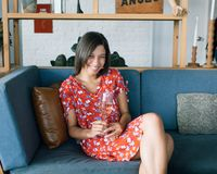 Woman Sitting at Sofa Wearing Red and Multicolored Floral Dress White Holding Glass Stock Images