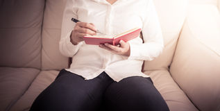 Woman is sitting on a sofa and writing notes in a notebook Stock Photos
