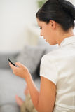 Woman sitting on sofa and writing sms on mobile Stock Photography