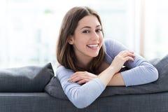 Woman sitting on sofa Stock Photos