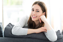 Woman sitting on sofa Royalty Free Stock Image