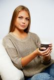 Woman sitting on a sofa Stock Photography