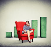 Woman sitting in soft red chair over rising chart background Stock Photo