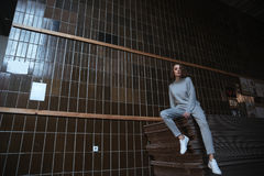Woman sitting on some wood sheets. Full-length shot of woman with curly hair in sportsuit sitting on some wood sheets in museum Royalty Free Stock Photography