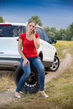 Woman sitting on the spare tire at roadside and calling for help Royalty Free Stock Photo