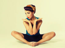 Woman sitting on the splits. A woman in a headscarf sitting in the lotus position Royalty Free Stock Photo