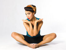Woman sitting on the splits. A woman in a headscarf sitting in the lotus position Stock Images