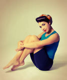 Woman sitting in sport clothes in retro style. Beautiful brunette sitting on the floor hugging his knees Royalty Free Stock Photo