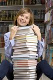 Woman sitting with stack of  books Royalty Free Stock Images