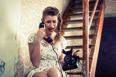 Woman sitting on the stairs and crying on the phone Stock Image