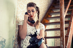 Woman sitting on the stairs and crying on the phone Stock Images
