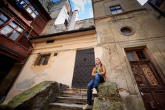 Woman sitting on the stairs of an old building in the city Stock Image