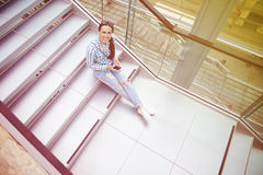 Woman sitting on the stairs with smartphone Stock Photo