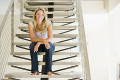 Woman sitting on stairs smiling Royalty Free Stock Photos