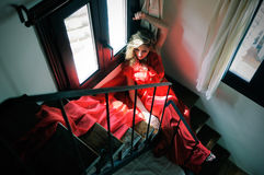 Woman sitting in stairs wearing a red dress Stock Photos