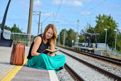Woman sitting on the station and reading Stock Photo
