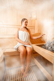 Woman sitting in steamed sauna next to oven Stock Images